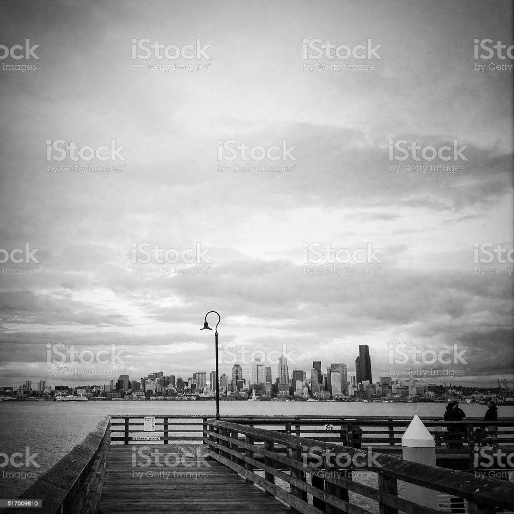 Monochrome distant city from pier stock photo