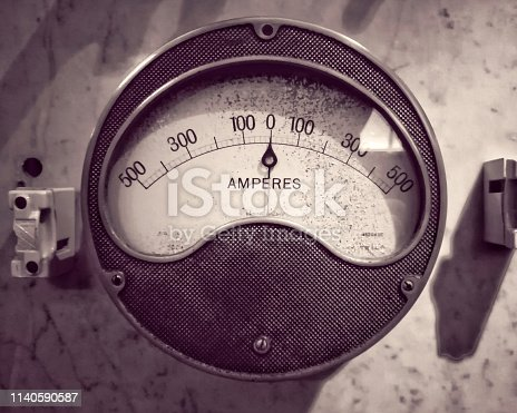 monochrome image of an old round metal industrial ammeter with an analogue dial and scale