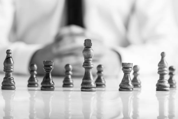 Monochrome image of businessman sitting in front of dark chess pieces stock photo