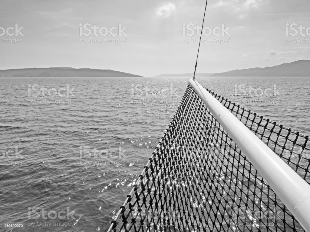 Monochrome image of Croatian islands in the Adriatic Sea with a ship's bow in the foreground stock photo