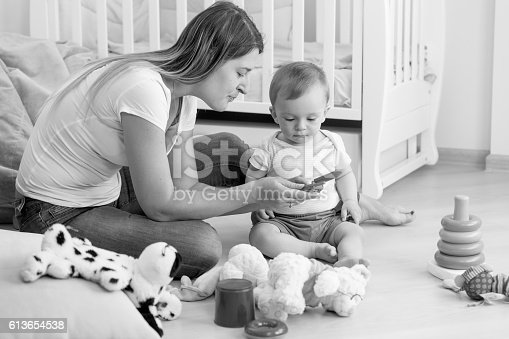 istock Monochrome image of mother playing with her baby on floor 613654538
