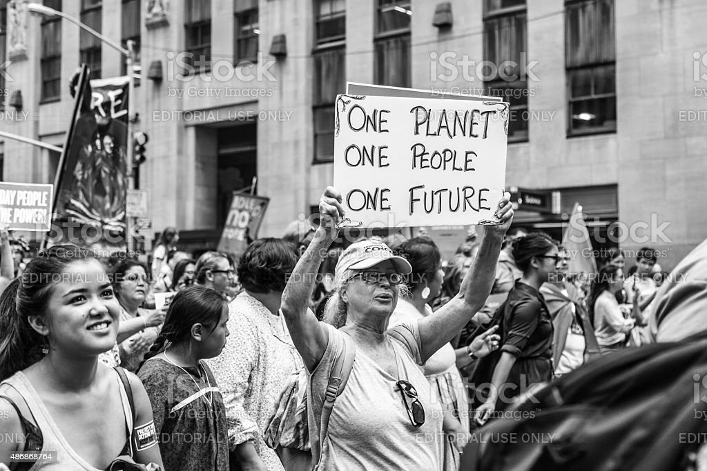 Monochrome image of woman carrying a placard at PCM, NY New York, USA -  September 21, 2014: Woman carries a placard reading One Planet, One People, One Future at the international Peoples Climate March demonstrating against global climate change and environmental degradation, Manhattan, New York, September 2014.  2014 Stock Photo