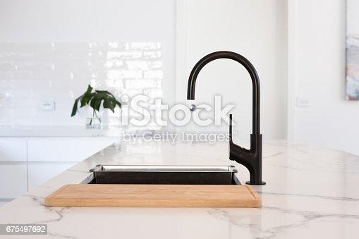 Monochrome kitchen detail of black gooseneck tap set in a white marble counter top