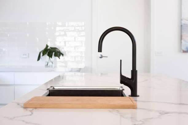 Monochrome kitchen detail of black gooseneck tap stock photo
