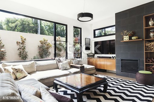 istock Monochrome living room with wood and grey tiling accents 876786836