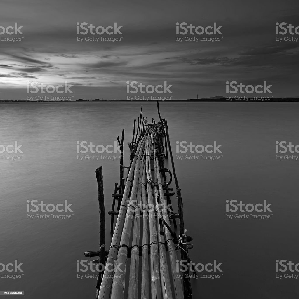 Monochrome of bamboo pier bridge at beautiful sunset stock photo
