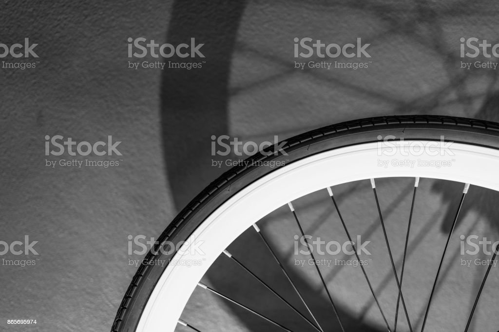 Monochrome of bicycle wheel with light and shadow, bicycle part, close up details, vintage background. stock photo