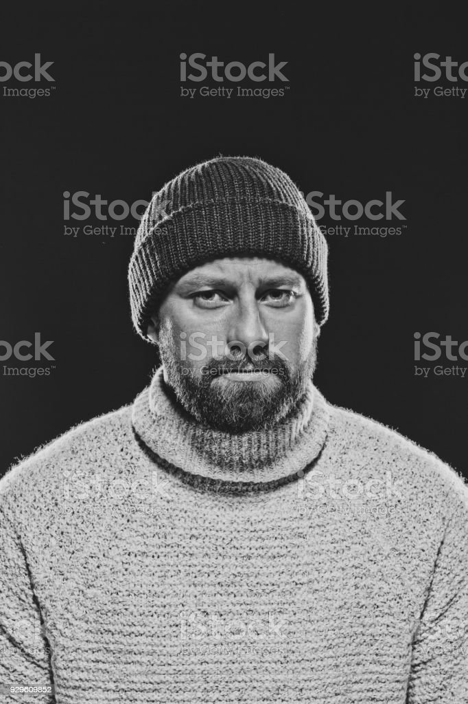 Monochrome portrait of bearded, handsome man against dark background Monochrome portrait of bearded, handsome man wearing sweater and beanie hat, looking at camera. Studio shot, black background. 30-34 Years Stock Photo