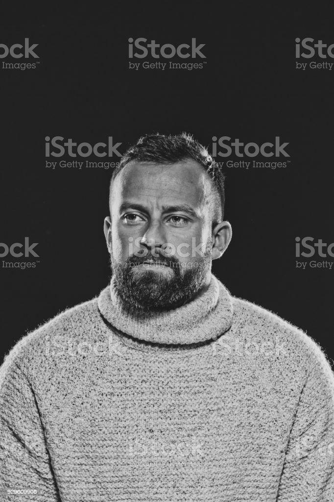 Monochrome portrait of bearded, handsome man against dark background Monochrome portrait of bearded, handsome man wearing sweater. Studio shot, black background. 30-34 Years Stock Photo