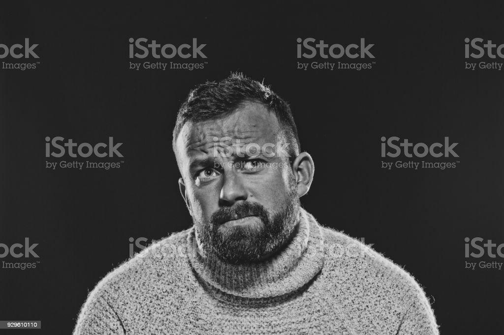 Monochrome portrait of bearded, handsome man against dark background Monochrome portrait of pensive, bearded man wearing sweater. Studio shot, black background. 30-34 Years Stock Photo