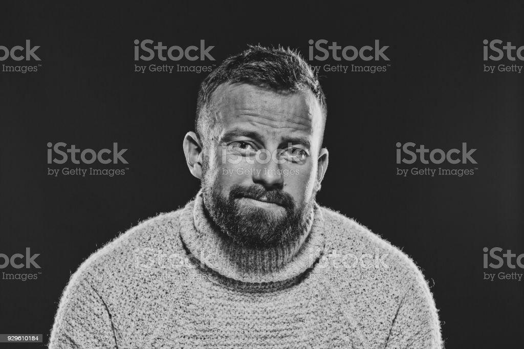 Monochrome portrait of bearded, handsome man against dark background Monochrome portrait of bearded, handsome man wearing sweater smirking at camera. Studio shot, black background. 30-34 Years Stock Photo
