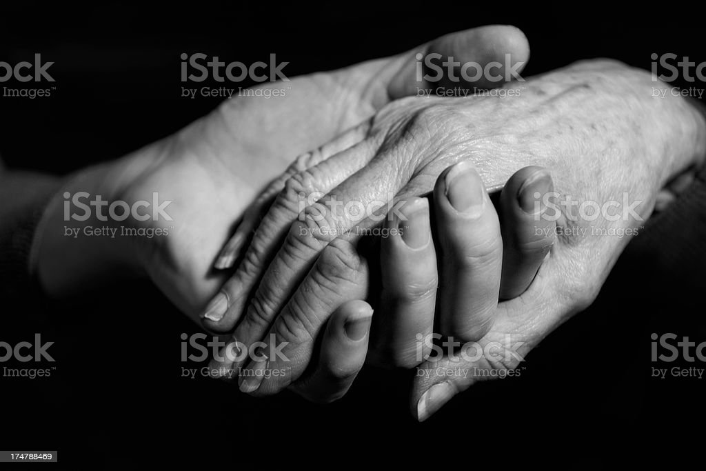 Monochrome Shot Of Young Woman Holding Older Woman's Hand stock photo