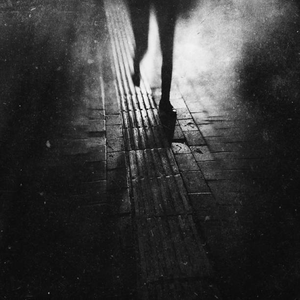 Monochrome textured view of a woman walking at the night