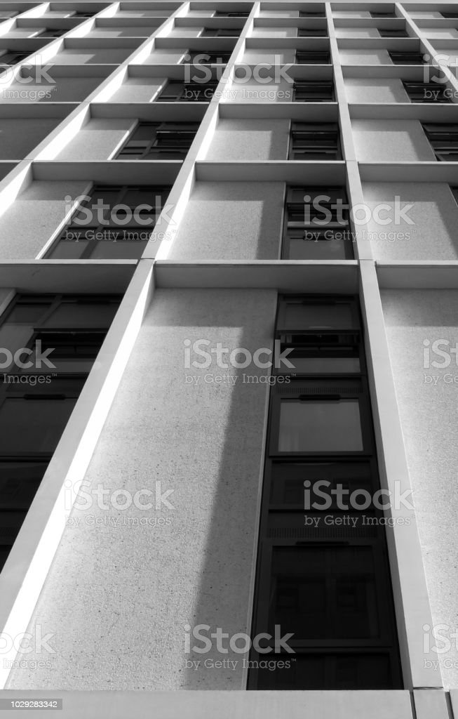 monochrome vertical view of a tall concrete angular modern high building with geometric white details stock photo