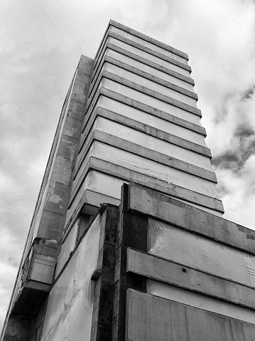 a monochrome vertical view of an abandoned derelict old concrete high-rise commercial building with blocked up windows against a cloudy sky