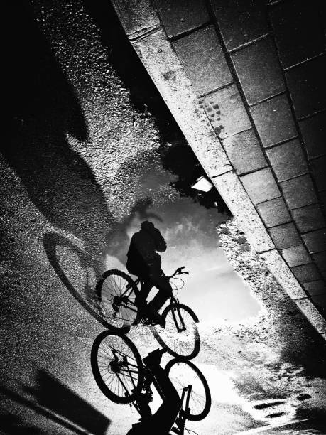 Monochrome view of cyclist reflection and shadow