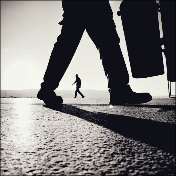 Monochrome view silhouettes of two men walking in the street