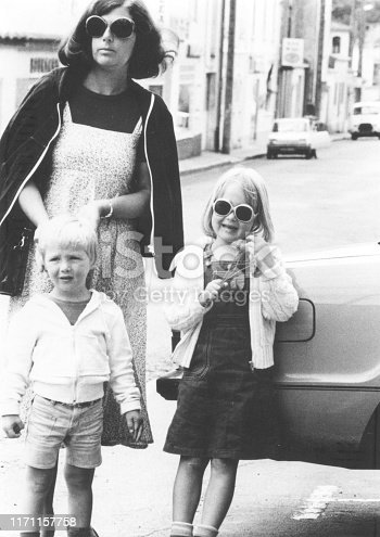Monochrome vintage 1970s image: mother wearing sunglasses, running errands with her young daughter and son.