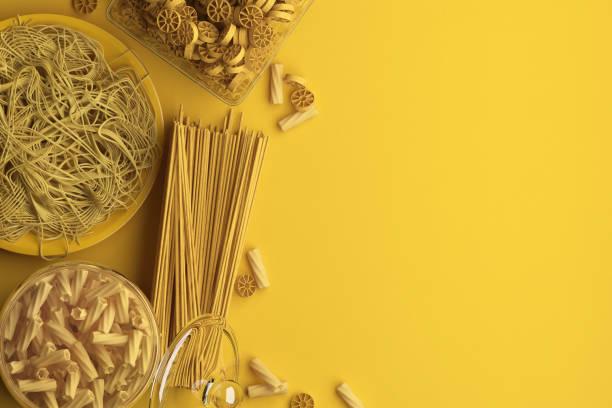 monochrome gelbe komposition aus trockenen und gekochten nudeln und spaghetti auf gelbem hintergrund. banner mit kopierplatz für text. ein satz essen auf der oberen ansicht. - pasta deli stock-fotos und bilder