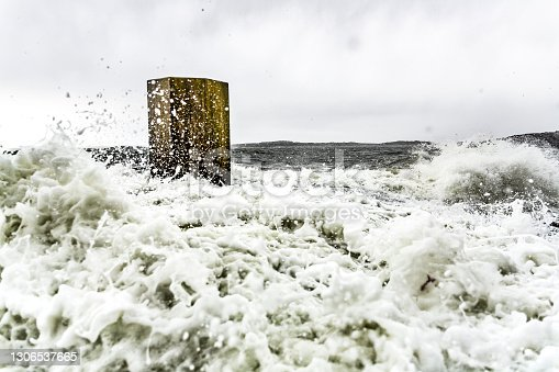 Concrete monolith by raging sea during heavy storm