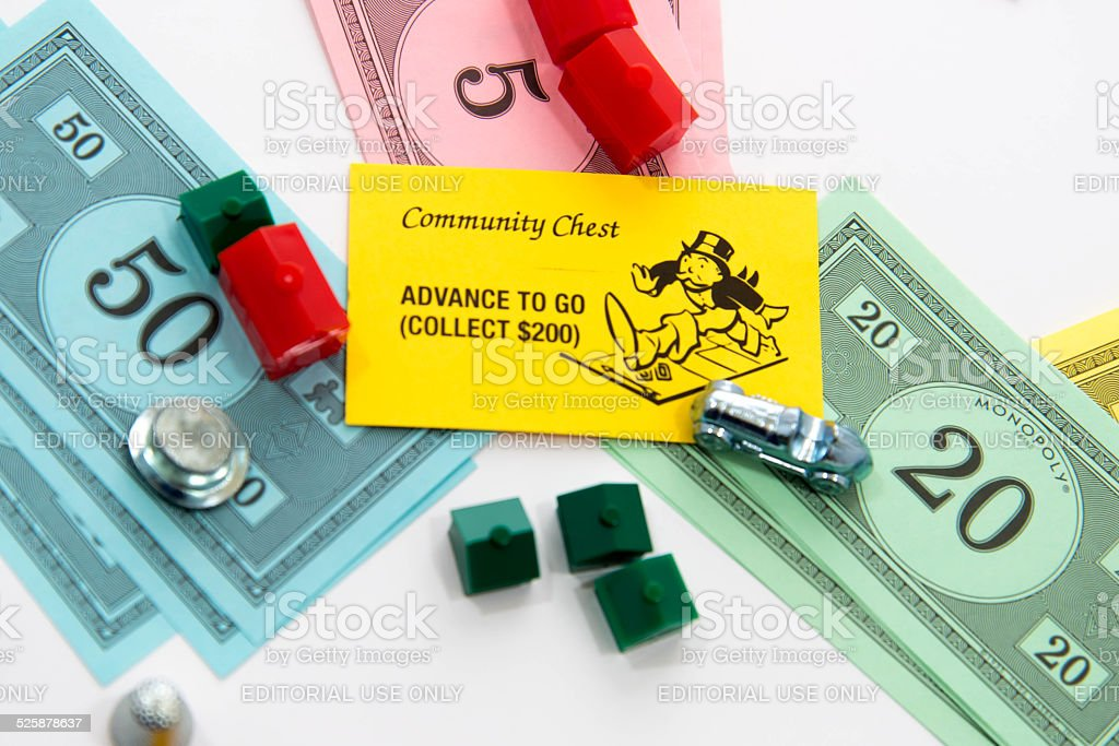 Monopoly - Advance To Go card, money, playing pieces stock photo