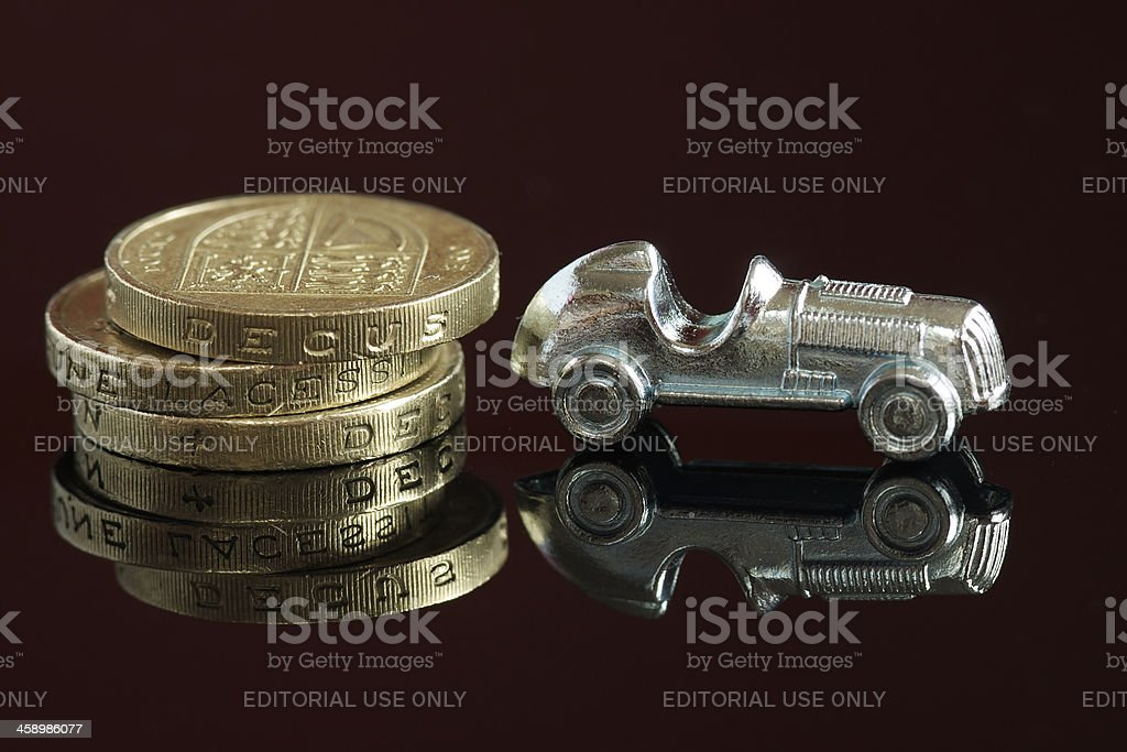 Monopoly car and one pound coins royalty-free stock photo