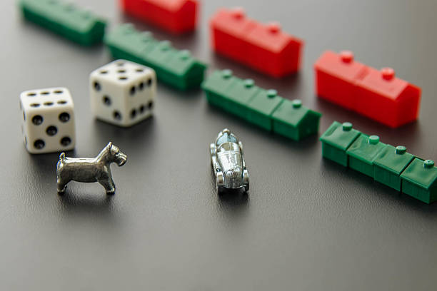 Monopoly - car, dog, dice, hotels and houses stock photo
