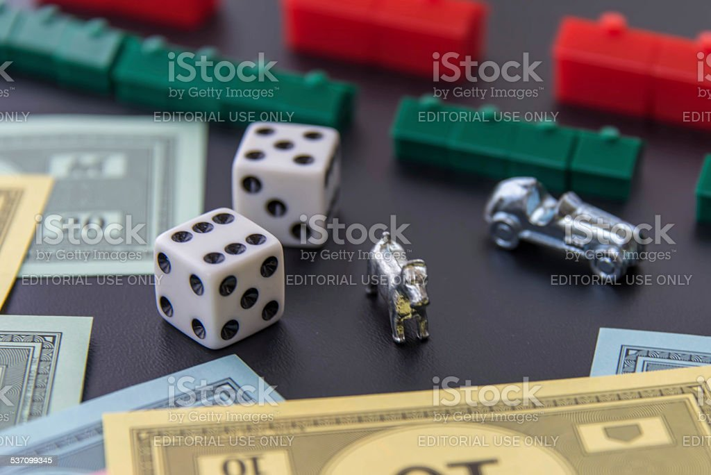 Monopoly - car, dog, dice, houses, hotels and money stock photo