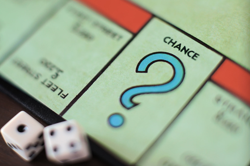 Durham, England - December 31, 2011: Two dice on the CHANCE space on the British version of the Parker Brothers board game of Monopoly. Parker Brothers, a subsidiary of Hasbro, has produced the game since 1935. It is the most successful board game in history.