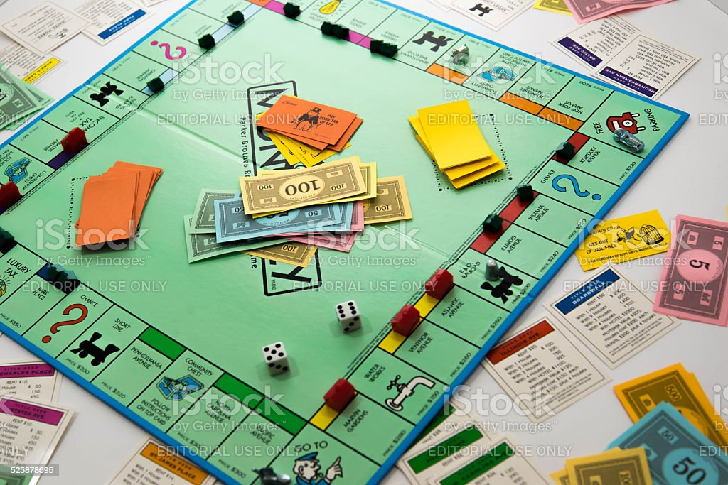Monopoly game in play - money, dice, pieces and cards stock photo
