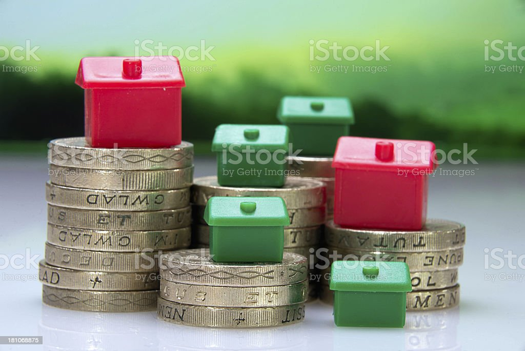 Monopoly house pieces on coins stock photo