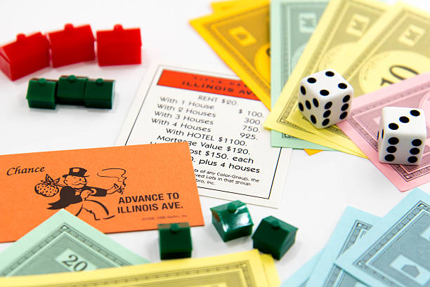 Monopoly - Illinois Ave card, pieces, money, hotels and houses stock photo