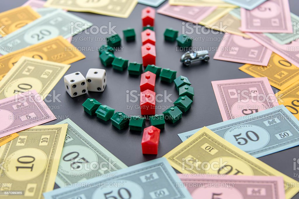 Monopoly - money around the car, dice, houses and hotels stock photo