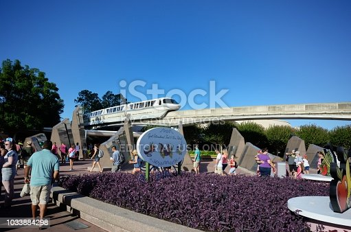 Orlando, Florida, USA - September 2, 2018: Walt Disney World Monorail traveling through Epcot near gates in Orlando, Florida.  Sign for International Food and Wine Festival in foreground.