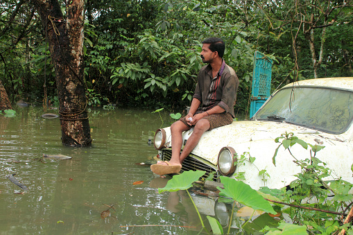 Aranmula, India - August 06,2013:Unidentified man sits on a car in the flood water in Aranmula,Kerala, India. Kerala is the most rain affected state on south west monsoon in India