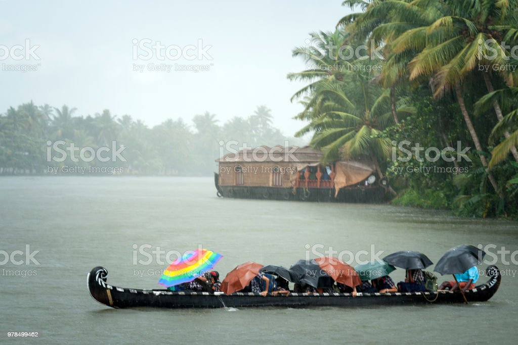 Monsoon time. People crossing a river by boat in rain with umbrellas