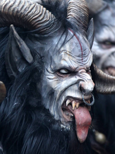 monster mask during santa klaus parade - demon stock photos and pictures
