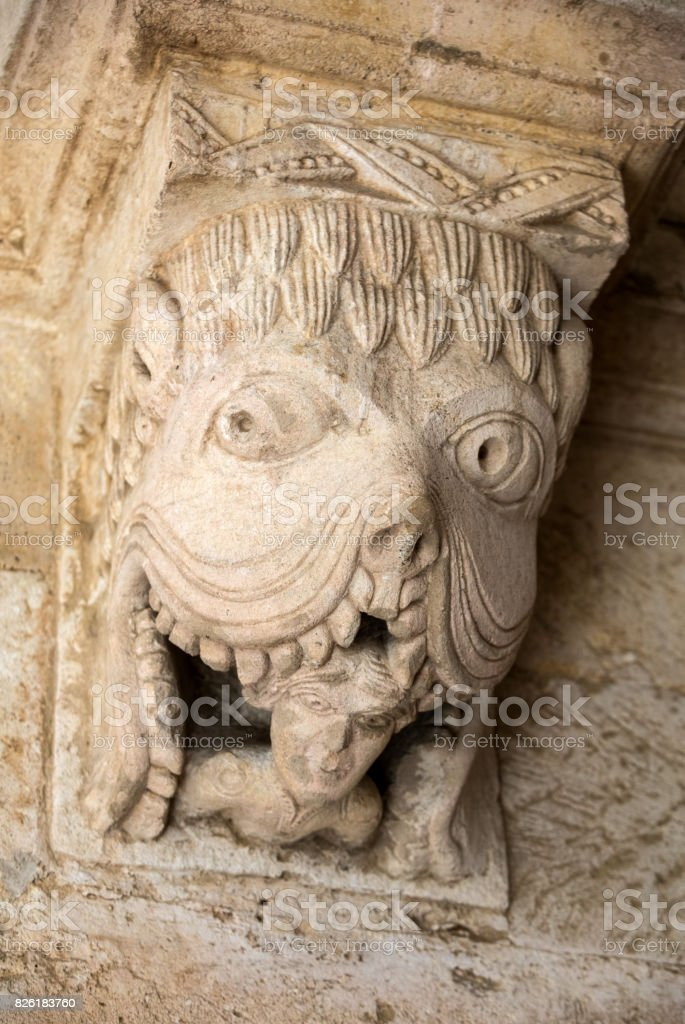 Monster or Tarasque Devouring a Sinner c12th Romanesque Carving in the Cloisters Montmajour Abbey near Arles Provence France stock photo