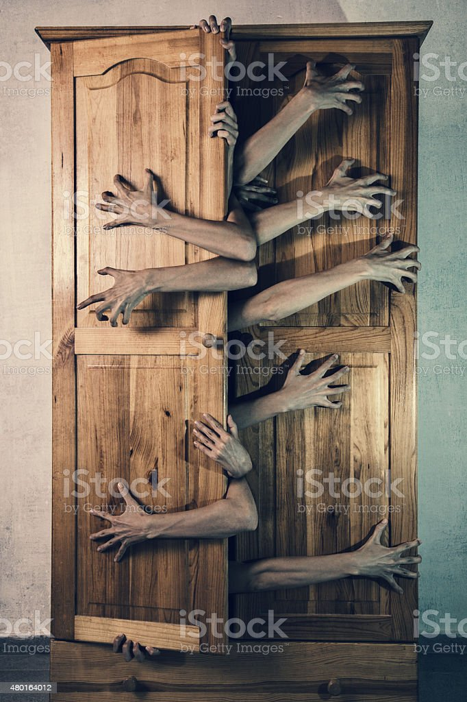 Monster with lot of hands trying to escape from cupboard stock photo