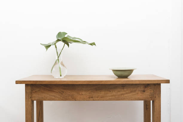 Monstera leaves in glass vase with green bowl on oak table stock photo