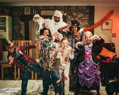 Friends of mixed ages and ethnicities dressed in costumes reaching out towards the camera like zombies.