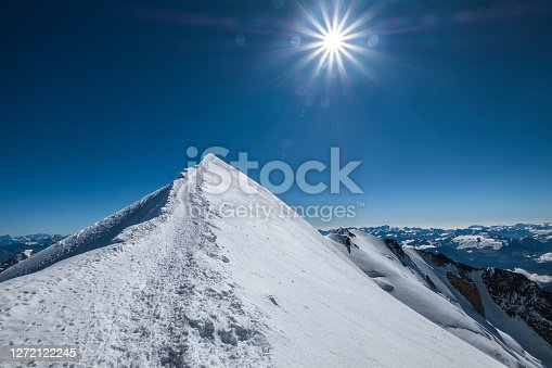 istock Mont Blanc (Monte Bianco) snowy 4808m summit wide angle view with surrounded French Alps landscape with deep blue sky and bright midday sun. Popular nature landmarks concept image. 1272122245