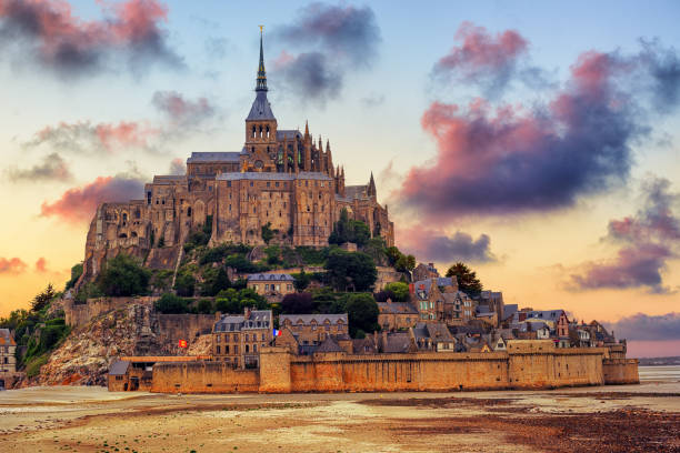 mont saint michel island, normandy, france, on sunset - unesco foto e immagini stock