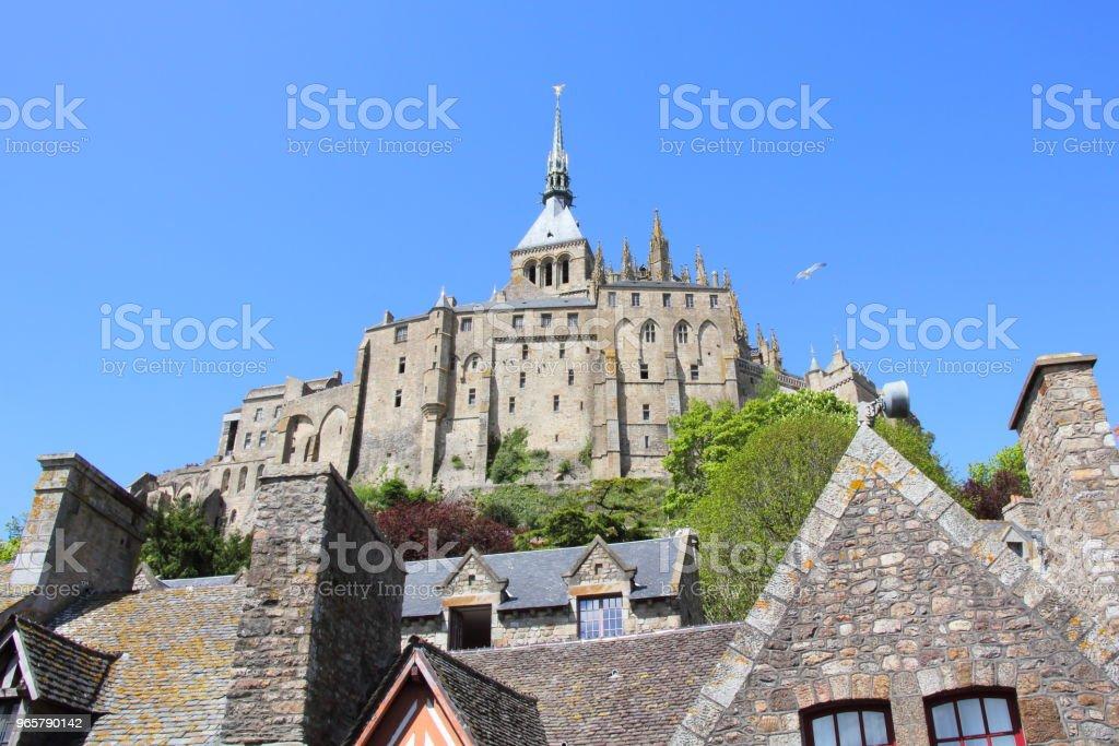 Mont Saint-Michel above the village rooftops. - Стоковые фото Аббатство роялти-фри