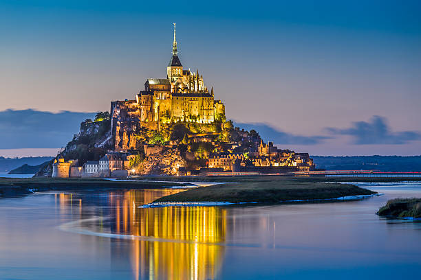 Mont Saint-Michel in twilight at dusk, Normandy, France Beautiful view of famous Le Mont Saint-Michel tidal island in beautiful twilight during blue hour at dusk, Normandy, northern France. manche stock pictures, royalty-free photos & images