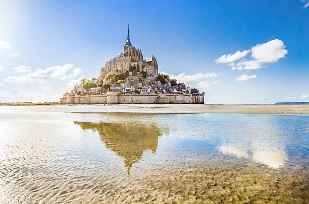 Mont Saint-Michel, Normandy, France Panoramic view of famous Le Mont Saint-Michel tidal island on a sunny day with blue sky and clouds, Normandy, northern France. manche stock pictures, royalty-free photos & images
