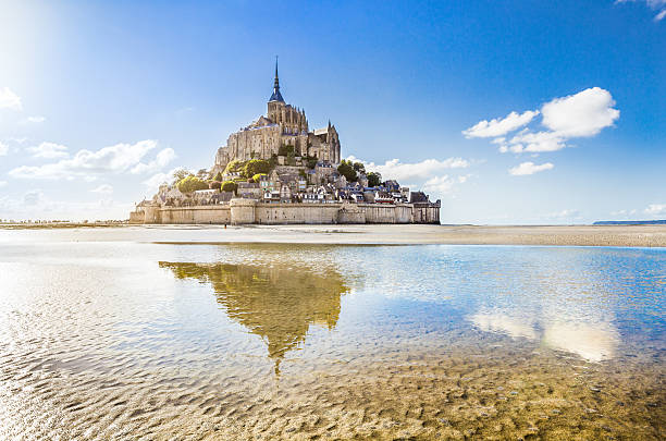 Mont Saint-Michel, Normandy, France Panoramic view of famous Le Mont Saint-Michel tidal island on a sunny day with blue sky and clouds, Normandy, northern France. normandy stock pictures, royalty-free photos & images