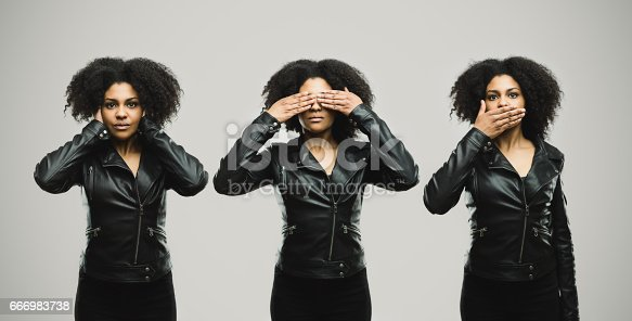 Montage of a young stylish woman covering her eye, ears and mouth with hands. Horizontal portrait of real black woman gesturing hear no evil, see no evil and speak no evil against gray background. Studio photography from a DSLR camera. Sharp focus on eyes.