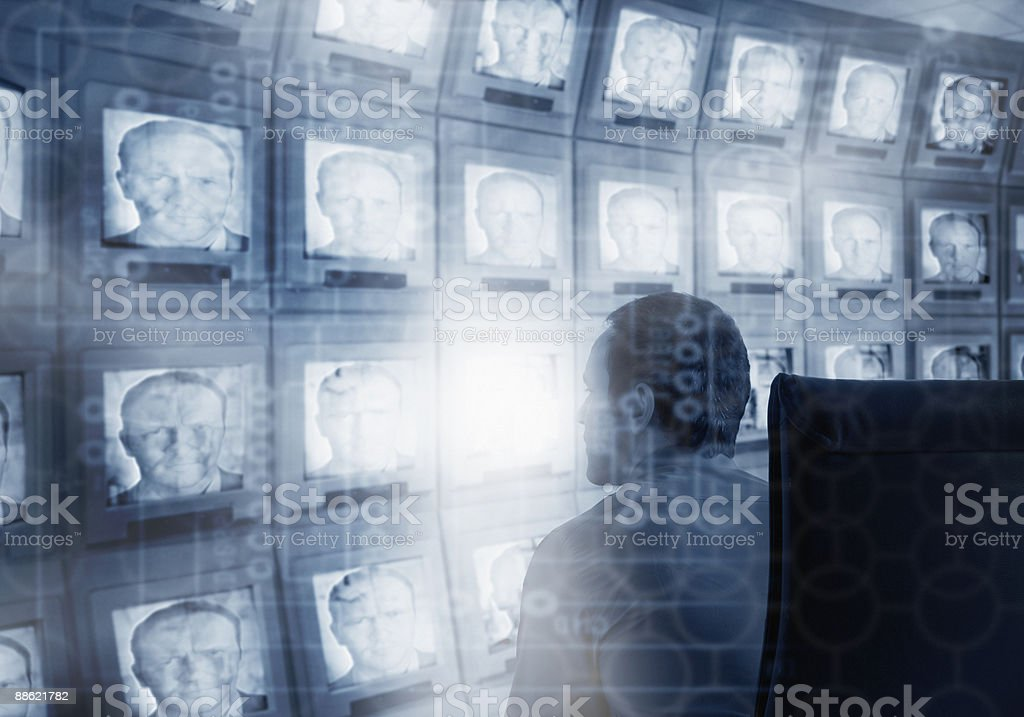 Montage of man, microchip and bank of compute monitors royalty-free stock photo