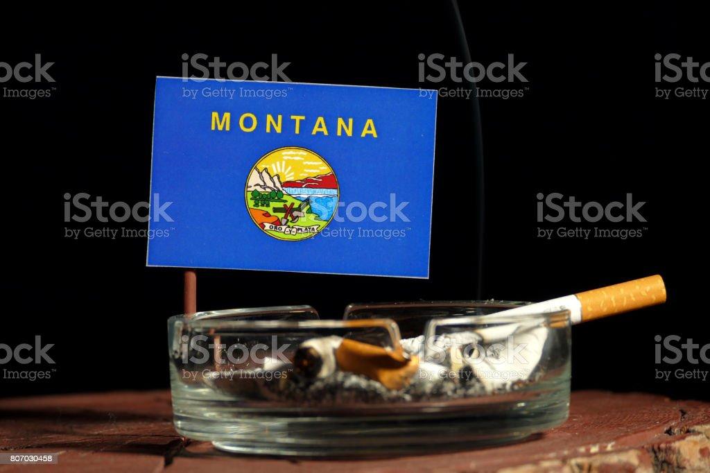 Bandeira de Montana com queima de cigarro no cinzeiro isolado no fundo preto - foto de acervo